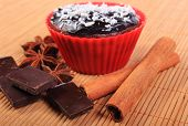 image of chocolate muffin  - Homemade delicious fresh baked chocolate muffins with desiccated coconut in red silicone cups pieces of chocolate star anise and stick of cinnamon - JPG
