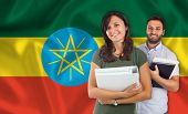stock photo of babylon  - Couple of young students with books over Ethiopian flag - JPG