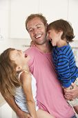 picture of cuddle  - Father Giving Children Cuddle At Home - JPG