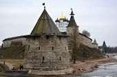 stock photo of fortified wall  - Stone tower and Pskov Kremlin fortress wall at the confluence of two rivers - JPG