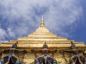 stock photo of glorify  - Titans and monleys carry golden pagoda decoration in temple of emerald Buddha - JPG