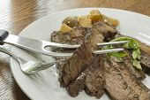foto of flank steak  - Sliced juicy skirt steak with potatoes and arugula garnish - JPG