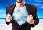 stock photo of brazilian money  - Businessman stretching suit with Brazilian money on beach background - JPG