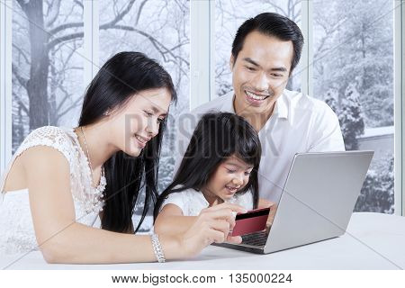 Cheerful family shopping online using laptop and paying with credit card at home