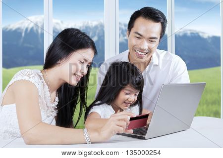 Happy family using credit card for paying online while looking at laptop computer at home