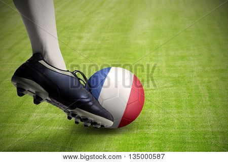 Close up of foot kicking a soccer ball with national flag of France at the grass field
