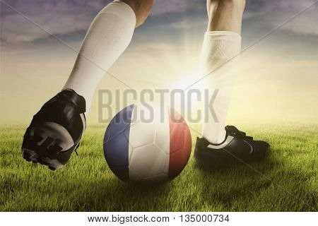 Foot of soccer player wearing football shoes while playing a ball on the field with national flag of France