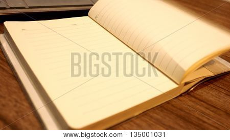 Note Book Opening and key board on wood desk photo moving blur.