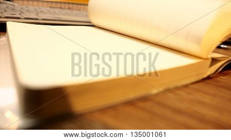 Note Book Opening and key board on wood desk background blur.