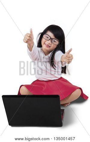 Portrait of pretty little girl showing thumbs up while sitting in the studio with laptop computer on the floor