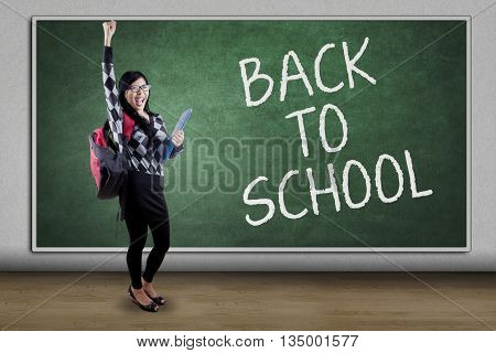 Joyful female high school student raising hand in the class with text of Back to school on the blackboard