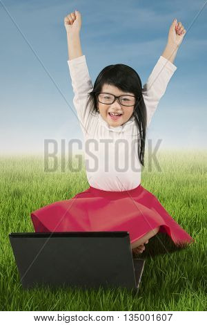 Picture of joyful little girl raising hands on the meadow while wearing glasses with laptop computer on the grass