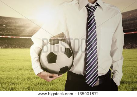 Close up of a man wearing formal suit at the field while holding a soccer ball