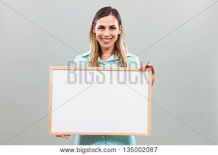 Beautiful nurse  is holding whiteboard and looking at camera.