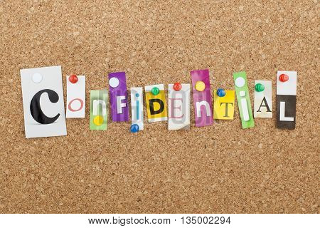 Confidential word as letters pinned on cork board