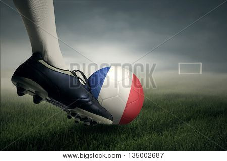 Foot of soccer player kicking a ball with flag of France toward a goal post at the field