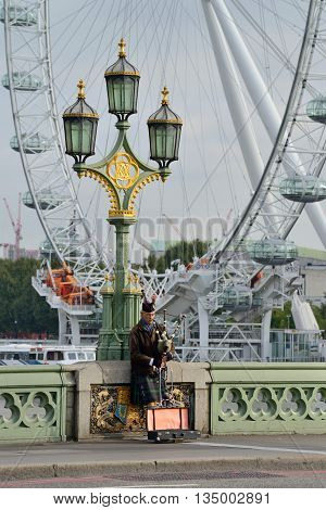 LONDON - OCTOBER 04: unidentified bagpiper on the Westminster Bridge on October 04 2014 in London UK. London is one of the world's leading tourism destinations.