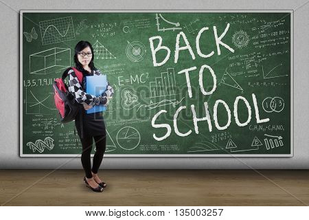 Pretty female high school student standing in the classroom with doodles and text of Back to School on the blackboard