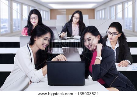 Portrait of two female worker discussing a job on the laptop and other employee busy working in office