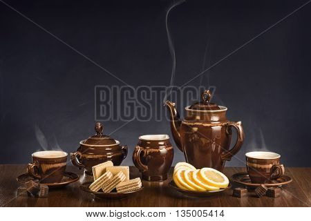 Hot coffee in cups and a dessert on a table against a dark background