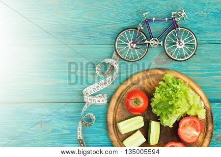 Bicycle Model, Fresh Vegetables And Centimeter Tape On Blue Wooden Desk