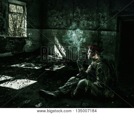 war. weary soldier wearing military uniform with automatic riffle sitting at night in the destroyed building