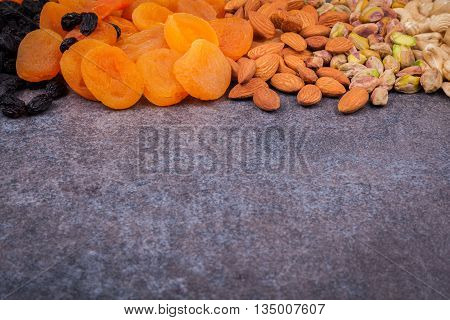 Dried fruit and nuts mixed and laid out on a dark background. Dried apricots, raisins, pistachios, almonds, cashew nuts on a dark background.