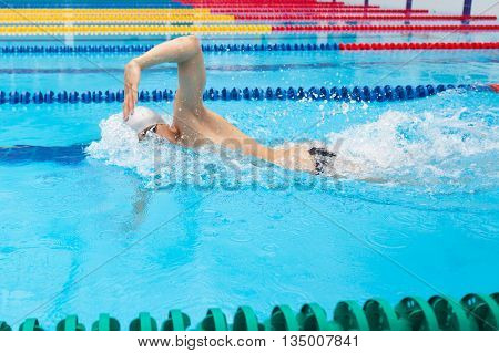 Man swimmer swimming crawl in blue water. Portrait of an athletic young male triathlete swimming crawl wearing a cap and swimming goggles while. Triathlete training for triathlon.