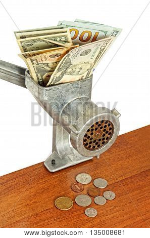Dollar banknotes in meat grinder and coins on wooden table.Money concept.