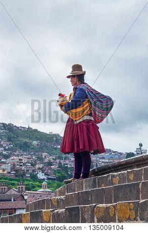 CUSCO PERU - MARCH 18 2015: Peruvian woman in traditional dresses on the street in Cuzco Peru