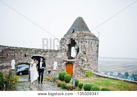 Wedding Couple Walking Under Rain With Umbrella Background Tower Of Old Castle