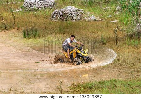 Off Road On 4X4 Quad Bike Through Mud Puddle