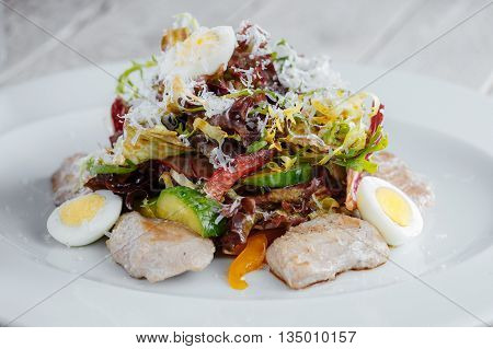 Salad On A White Plate With Vegetables, Eggs And Chicken