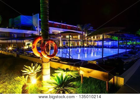 hotel with swimming pool and palm tree at night life preserver in foreground