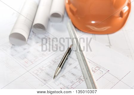 architectural plans project drawing and pen with blueprints rolls ruler and orange helmet architect engineering and contractor concept