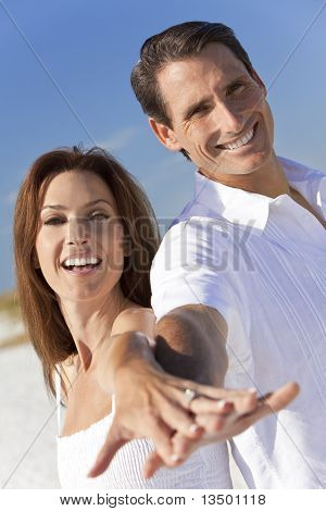 Attractive Couple Laughing Holding Hands On A Beach