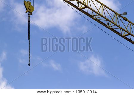 Crane ans construction site scaffolding element. Blue sky background. Construction or reconstruction concept