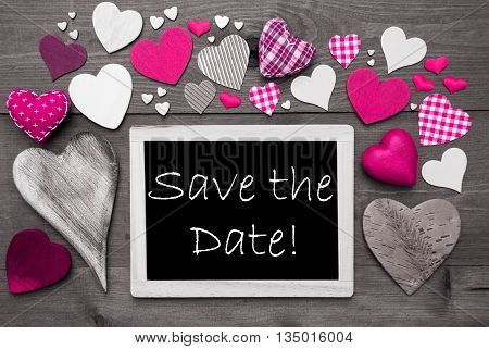 Chalkboard With English Text Save The Date. Many Pink Textile Hearts. Grey Wooden Background With Vintage, Rustic Or Retro Style. Black And White Style With Colored Hot Spots