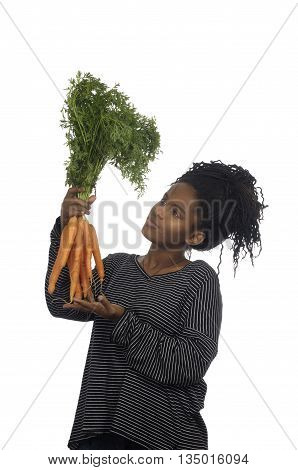 Teenage girl playing with a carrot on white background