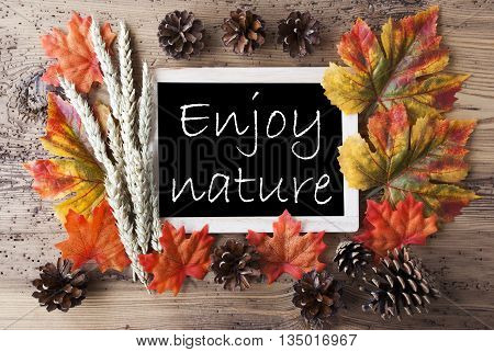 Blackboard With Autumn Or Fall Decoration. Greeting Card For Seasons Greetings. Colorful Leaves, Fir Cone And Barley On Aged Wooden Background. English Quote Enjoy Nature