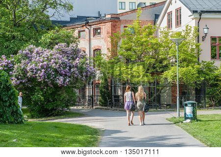 NORRKOPING, SWEDEN - JULY 14, 2010: Two young women walk in a city park Stromparken on a sunny summer afternoon. Norrkoping is a historic industrial town.