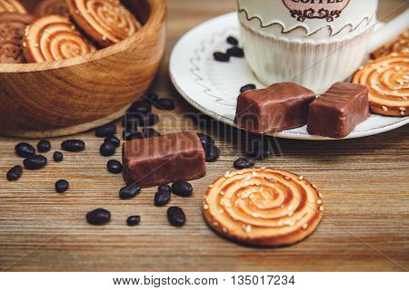 There are Cookies,Candy,Chocolate Peas,Poppy;Porcelain Saucer and Cap with Coffe,Tasty Sweet Food on the Wooden Background.Toned