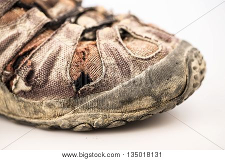 detail of old damaged hike shoe on white background