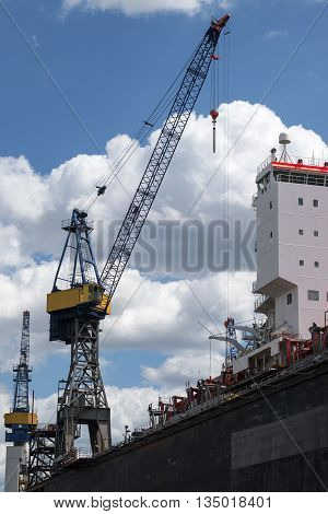 cargo port crane and control tower against the blue sky with clouds at a quay in Hamburg Germany vertical low angle shot