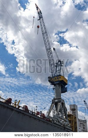 Cargo crane against the blue sky with clouds in the port of Hamburg Germany vertical low angle shot copy space