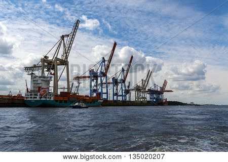 Hamburg, Germany - June 11, 2016: cranes and a container ship in the international cargo port of Hamburg river Elbe blue sky with clouds copy space