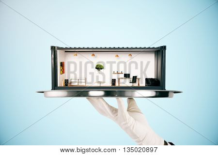 Hand holding metal tray with creative office interior inside cargo container on light blue background. 3D Rendering