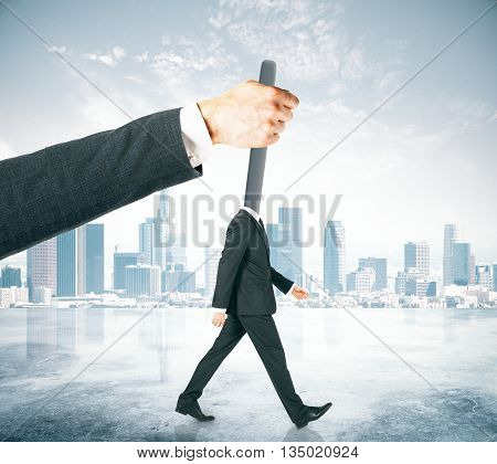 Hand manipulating lever-headed businessman on abstract city background. Concept of control