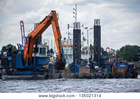 Hamburg Germany - June 11 2016: floating dredge deepens the fairway for large container ships at the cargo port of Hamburg in the river Elbe