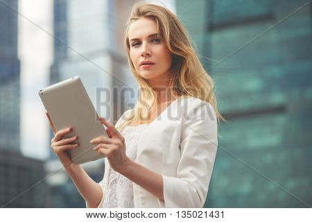 Beautiful woman using electronic tab in the street. Image toned in low contrast.